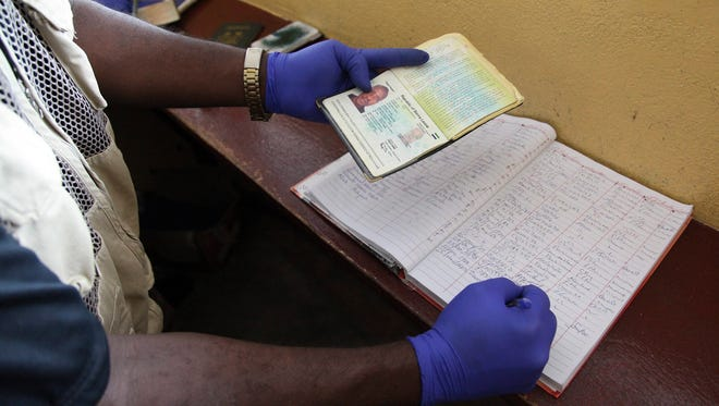 A Liberia immigration officer wearing gloves inspects a passport of a Sierra Leonean national at the Bo Waterside border post between Liberia and Sierra Leone on July 30, 2014.