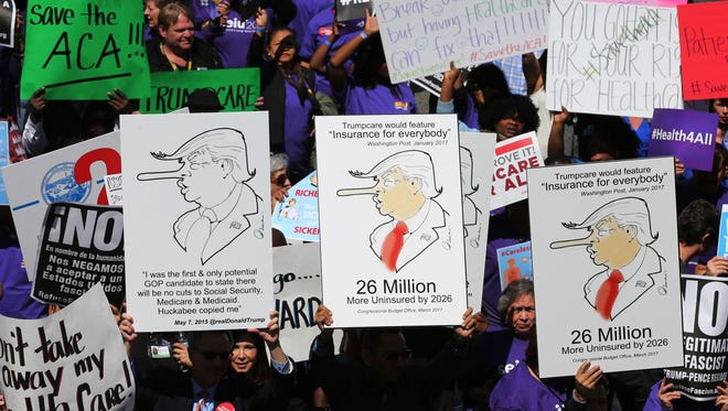 Hundreds of people march through downtown Los Angeles protesting President Donald Trump's plan to dismantle the Affordable Care Act, his predecessor's signature health care law, Thursday, March 23, 2017. The demonstration came as U.S. congressional leaders postponed a vote on the American Health Care Act, which the White House hopes will replace Obamacare. (AP Photo/Reed Saxon)