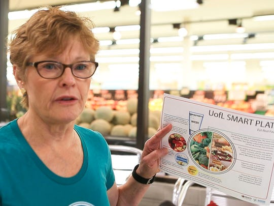 Dietitian Karen Newton holds up a copy of the Smart Plate graphic that's been touted for U of L students.