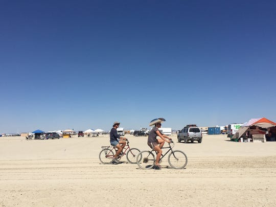 Early arrivers to Burning Man ride their bikes on the playa on Thursday August 25, 2016.