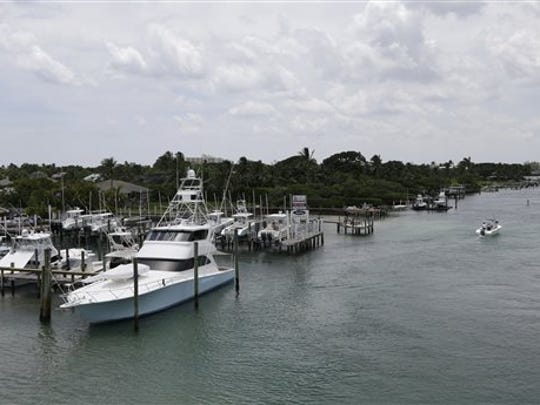 A boat heads out from the JIB Club Marina down the Indian River, Tuesday, July 28, 2015, in Tequesta, Fla. Two Florida teens who have been missing since Friday, July 24, were last seen fueling their boat at this marina before heading out to fish. The search continues for the boys from the Atlantic waters off Daytona Beach, Fla., north through Savannah, Ga.