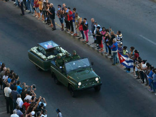 Placed in a small coffin covered by a Cuban flag the ashes of Cuban leader Fidel Castro are driven along the streets of Havana, Cuba, Wednesday Nov. 30, 2016. Castro's ashes have begun a four-day journey across Cuba from Havana to their final resting place in the eastern city of Santiago.