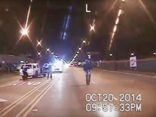 FILE - In this Oct. 20, 2014 frame from dash-cam video provided by the Chicago Police Department, Laquan McDonald, right, walks down the street moments before being fatally shot by CPD officer Jason Van Dyke sixteen times in Chicago. The Department of Justice is poised to release its report detailing the extent of civil rights violations committed by the Chicago Police Department. The next stage after the Friday, Jan. 13, 2017, release will be negotiations between the DOJ and the city.