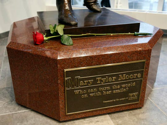 "A single rose sits on the base of the life-size bronze statue of Mary Tyler Moore at the Minneapolis Visitor Center, Wednesday, Jan. 25, 2017. Moore, 80, died Wednesday. The statue depicts her tossing her tam into the air as she did in the opening credits of ""The Mary Tyler Moore Show."""
