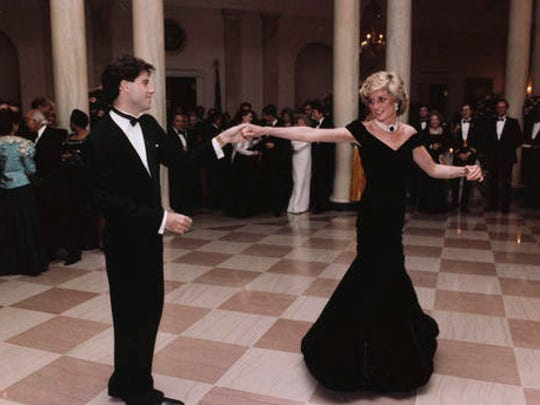 "FILE - In this Nov. 9, 1985 photo provided by the Ronald Reagan Library, actor John Travolta dances with Princess Diana at a White House dinner in Washington. This outfit is featured in an exhibition of 25 dresses and outfits worn by Diana entitled ""Diana: Her Fashion Story"" at Kensington Palace in London, opening on Friday, Feb. 24, 2017."