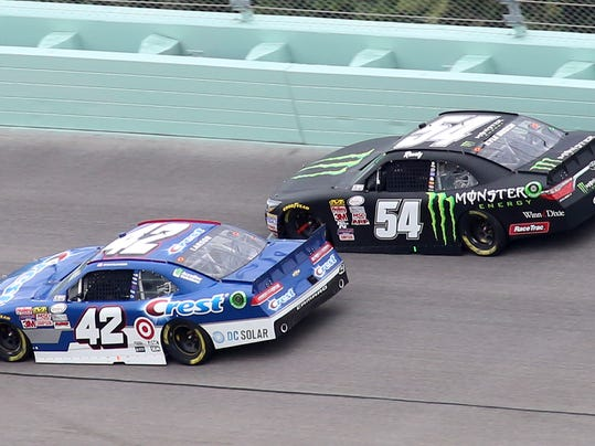 Kyle Larson (42) and Kyle Busch (54) take turn 2 during the NASCAR Xfinity Series auto race, Saturday, Nov. 21, 2015, at Homestead-Miami Speedway in Homestead, Fla. (AP Photo/Jim  Topper)
