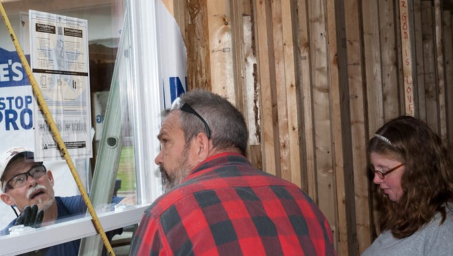 Larry Felts, left, and James Baltzer, center, work to install windows in a house for Habitat for Humanity Saturday. The home is being built for Heather Grayson, right.