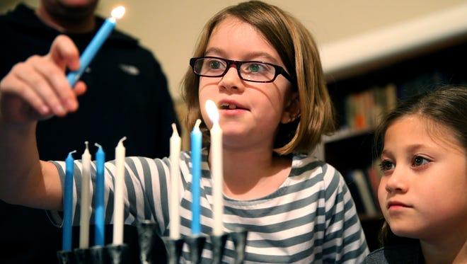 Children light menorahs during a Hanukkah celebration Friday at San Angelo's Congregation Beth-Israel.