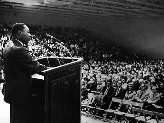 Martin Luther King Jr. addresses a crowded gymnasium