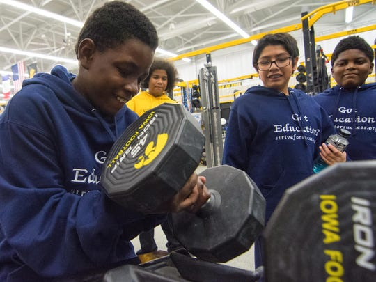 Tesean Henderson tries to lift a dumbell as Eric Fredieu, Damien Manzo, and Andre Johnson look on. The kids toured the Iowa Hawkeyes' football facilities with Strive For Success, a faith based tutoring program, Friday, Dec. 18, 2015.