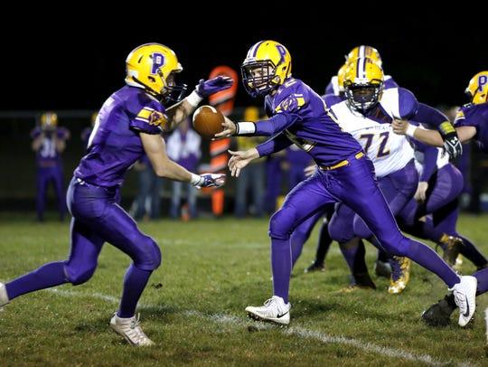 Pittsville quarterback Luke Denniston hands the ball