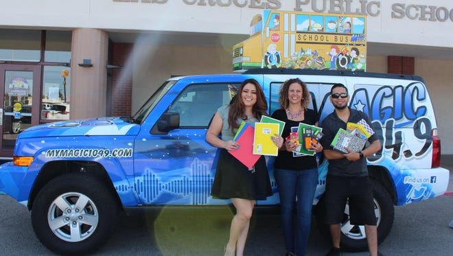 "Magic 104.9 radio personalities Patricia Valencia, left, and Ricky Tarin, right, pose with Las Cruces Public Schools Community Outreach Liaison Brigitte Zigelhofer, center. Magic 104.9 is currently hosting the ""Stuff the Bus"" school supply drive, now in its eighth year."