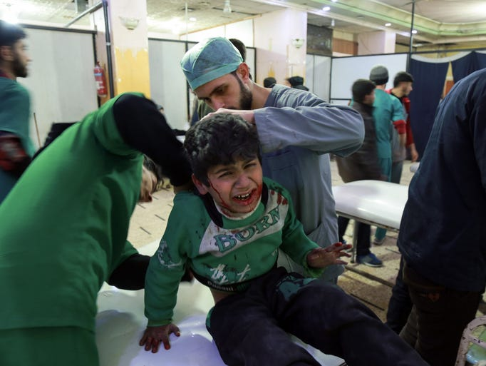 Paramedics tend to the injuries of a Syrian child who