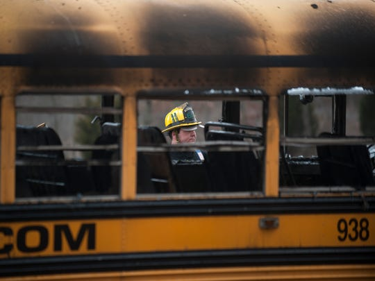 A firefighter works the scene of a bus fire that occurred