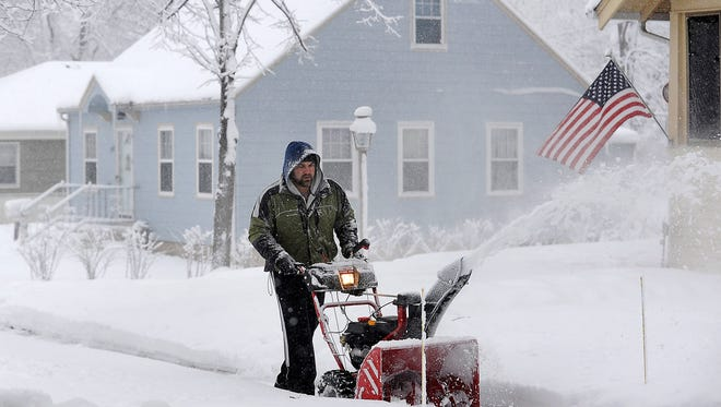 Zach Dynes blows snow along Spring Avenue in Sioux Falls, S.D., Friday, Jan. 8, 2016.