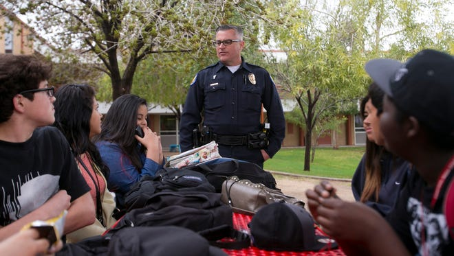 School Resource Officer John Harpster of the Phoenix Police Department talks to students during a lunch period at Central High School in Phoenix.