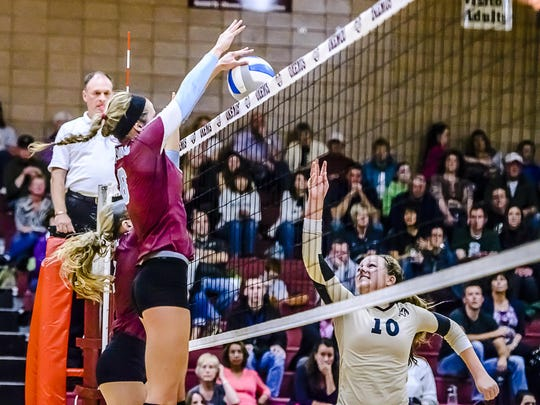 Daria Richards ,left, of Okemos taps a shot by Holt back to the Rams' side of the net to win their match.