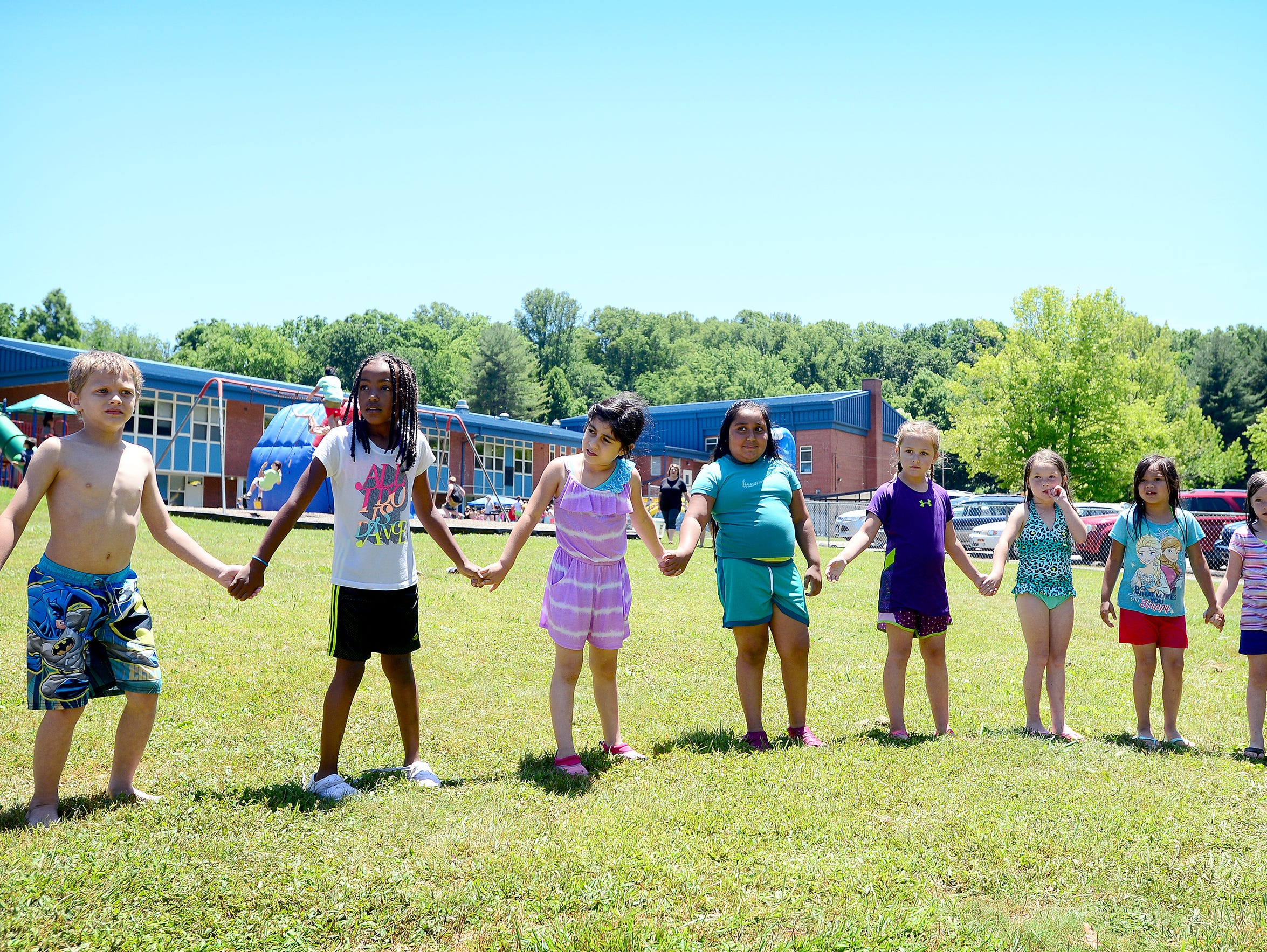 Students hold hands as they form a a circle to play