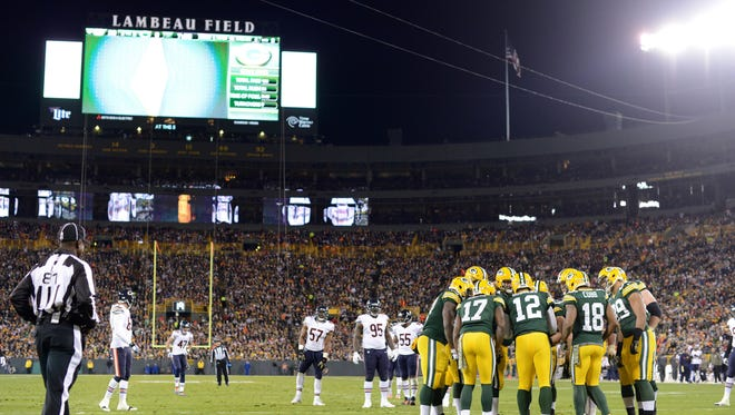 The Green Bay Packers offense huddles up at the start of a drive during their 55-14 victory over the Chicago Bears at Lambeau Field.