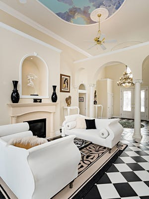 Along with ornate columns and dramatic arches, the living room features a medallion on the ceiling painted to look like a cloudy sky.