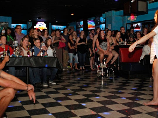 Patrons watch a performer at Fusion Night Club, which held a benefit Thursday to raise funds for victims of last weekend's mass shooting at Pulse Night Club in Orlando.