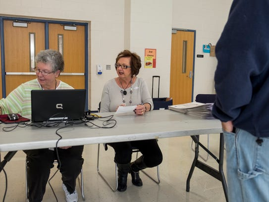 Joan Morrisson, left, and Saundra Heise check in voters