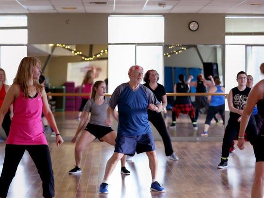Bob Zakes, 76, center, participates in a Zumba dance