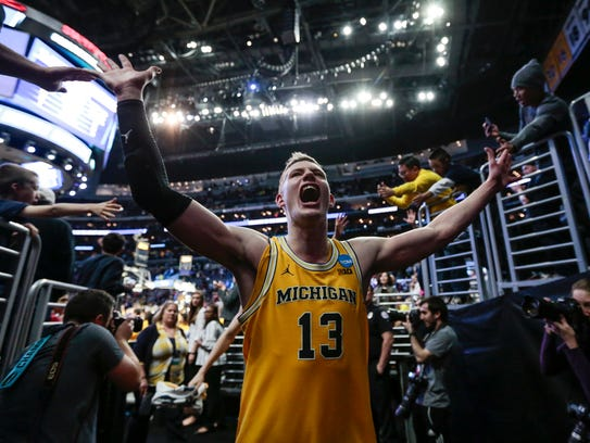 Moritz Wagner high-fives fans as he walks off the court