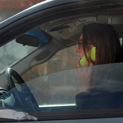 A motorist talks on her cell phone while driving along