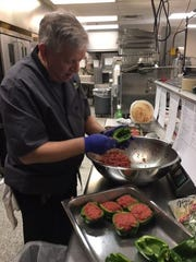 Ed Pickens, caterer and banquet owner of Ed Pickens Cafe on Main located downtown on the square, is retiring March 31. Heren he makes stuffed peppers for Columbia Gas Co. employees.