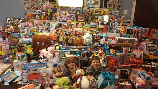 Chase Kemberling, left, and his brother, Travis Kemberling, sit among a sea of toys. Chase is a cancer survivor and was treated at the Hershey Medical Center. The Kemberling family of Lebanon has started a toy charity, Chasing a Cure. They raise funds to buy toys for the young patients at Hershey Medical Center and deliver loads of toys to the hospital every month.