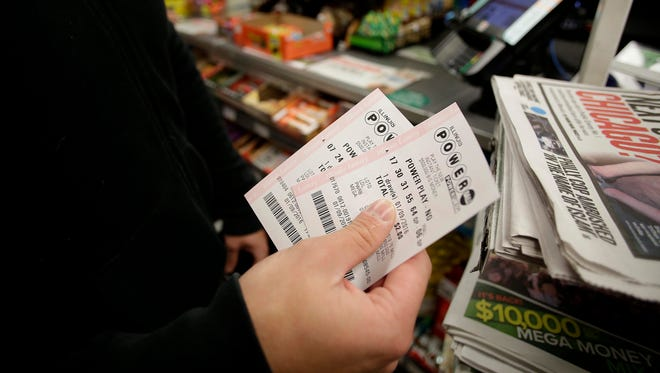 A customer shows off his Powerball tickets at a 7-Eleven store in Chicago on January 9, 2016.