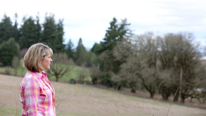 Leslie Edelblute stands on her property, looking out on an oak savanna that might have become a 12-acre solar farm. The solar farm applicants withdrew their proposal after protests from the neighbors.