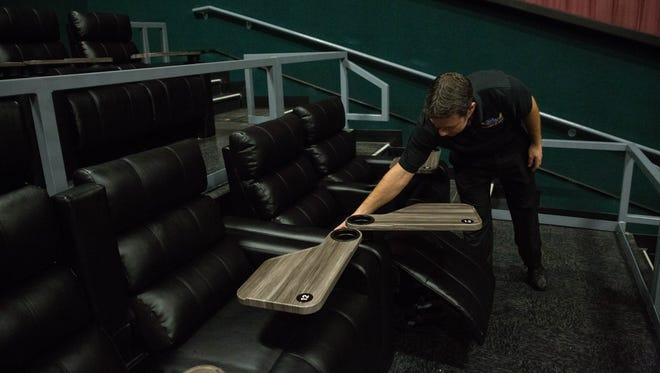 """Curt Young, head manager at Telshor 12 movie theater, demonstrates the new reclining """"love seats"""" in one of the remodeled auditoriums. Tuesday, April 25, 2017"""