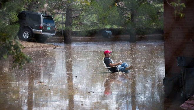 Doug Bickel takes a short break Thursday Aug. 24, 2017, while he helps his friend Mark Sale clean flood water after Wednesday night's storm in Hill, between Radium Springs and Doña Ana.