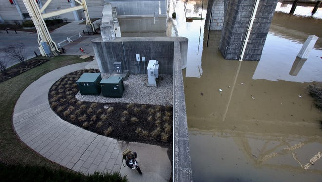 Eric Stemen walks on the south side of the flood wall where the Ohio River has overtaken River Road beneath the Second Street Bridge in Louisville, Kentucky.