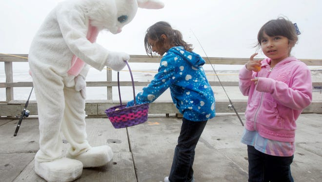 "Ninfa Gonzalez, 7, takes an egg from the Easter Bunny's basket as her sister, 5-year-old Estrella Gonzalez, opens up her egg Saturday, April 11, 2009, during a Fishing with the Easter Bunny event at Bob Hall Pier in Corpus Christi. The new owners of Pirate's Landing, the pier restaurant and tackle shop, held the event offering a free pancake breakfast or hot dog lunch for kids. The children also got to fish off the pier and reel in a bag of free goldfish to take home. ""People are really enjoying that its turning back into a family pier,"" said owner Glenn Laskowski, who said he plans to hold other family-friendly events. ""We know that once they (the children) get a taste for fishing they'll want to come back for more."""