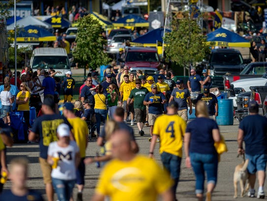 Fans walk between tailgates in a parking lot before