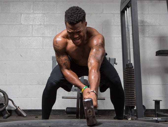 Isaiah Taylor performs an exercise involving a sledge