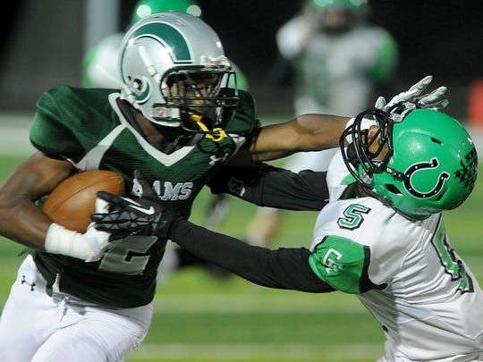 Madison's Tyrell Ajian stiff arms Clear Fork's Silas Finley on Friday at Madison High School.