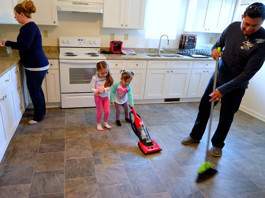 Tanya Cruz, left , daughters Eliana, 4, and Helena, 2, and Eliseo work on cleaning their soon-to-be home in Wrightsville that was built for them by Habitat for Humanity, Friday April 8, 2016. While not yet ready for move in, Habitat for Humanity will hold a dedication of the home Saturday. John A. Pavoncello photo