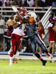 North Fort Myers' Joe Wilkins Jr. hold on to the ball to complete the pass under heavy defense from Dunbar's Tyrel Kennedy. Game highlights from the North Fort Myers at Dunbar football game.