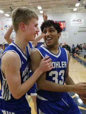 Kohler's Tyler Roeder and Mohsen Ali (33) celebrate following their team's 48-45 win over Howards Grove on Saturday.