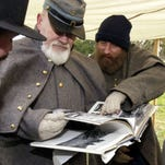 Tray Barr, right, and Andrew Atkins help carry Charles Henry during a medical demonstration in the Civil War reenactment at Mooney Grove Park on Saturday. Henry is playing the part of General Stonewall Jackson when he was accidentally shot by his own troops.