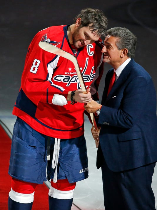 Washington Capitals left wing Alex Ovechkin (8) is presented a commemorative hockey stick by owner Ted Leonsis for becoming the fifth-fastest player in NHL history to reach the 500-goal milestone, before an NHL hockey game against the Vancouver Canucks, Thursday, Jan. 14, 2016, in Washington. (AP Photo/Alex Brandon)