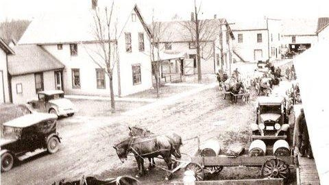 This photo shows farmers bringing and or picking up goods at the railroad depot, which is now the Enosburgh Historical Society museum. All of the houses on the other side of the street are gone and have been replaced by and Ace Hardware Store.
