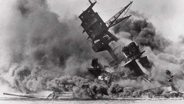This 1941 photo shows the terrible results of the Japanese attack on Pearl Harbor, as the USS Arizona went down in flames and smoke.
