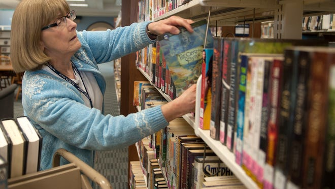 Ann Keener reshelves books Tuesday morning at the Mansfield-Richland County Library.
