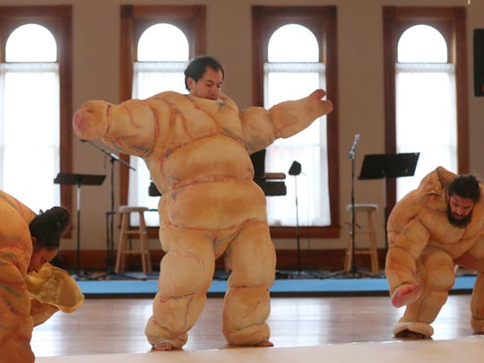Members of La Coperacha Puppet Co., Elisbeida Suarez, left, Alejandro Herrera, center, and Nicolas Pallares, slowly move their giant puppet costumes around the floor as the move through a segment of the show during their rehearsal for their upcoming performance of Don't Blame Anyone.