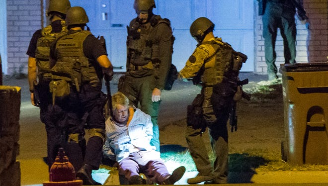 A shooting suspect sits on the curb after Las Cruces SWAT team members carried him out of the home he was barricaded in on the 1600 block of Gladys Drive. The suspect was unable to walk own his own.